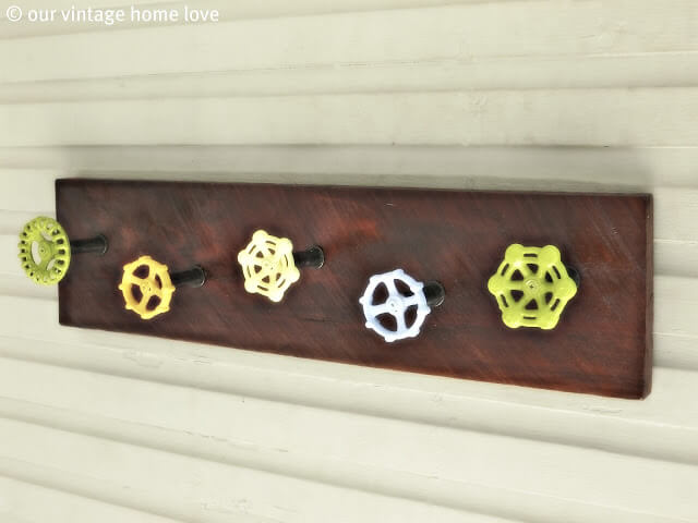 Wall-mounted wooden rack using painted vintage outdoor faucet knobs as pegs for hanging towels.