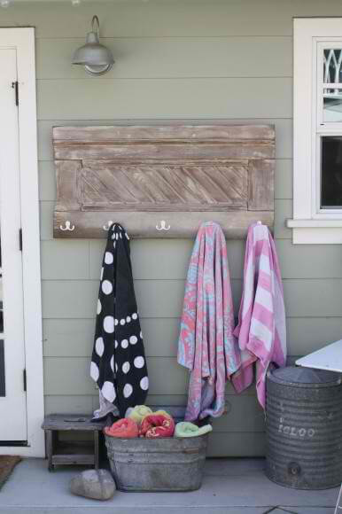 Wall-mounted towel rack with hooks made from cast off wooden architectural piece.
