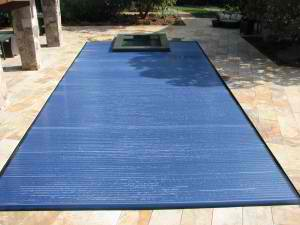 A rectangular pool covered by an automatic solar pool cover.