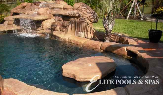 A large, natural stone table built inside a niche in the pool and surrounded by submerged bench seating.